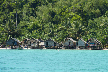 south park: The Moken Sea Gypsy Village at Koh Surin Tai in the Mu Ko National Park, Surin Islands of Thailand with its thatched houses on stilts.