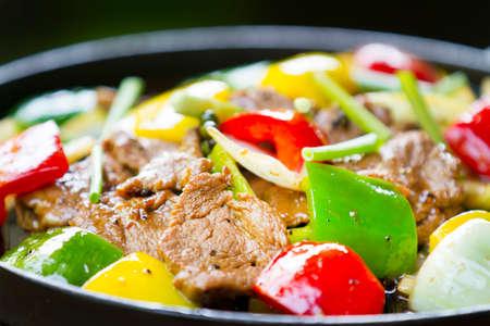 중국어 고추 스테이크 - 부드러운 쇠고기의 조각은 빨간색과 녹색 피망과 양파 볶음. 스톡 콘텐츠