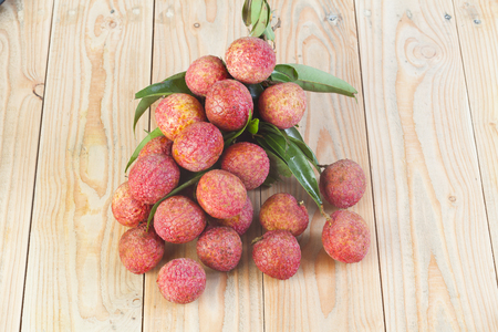 antecedents: fresh lychees on wooden background