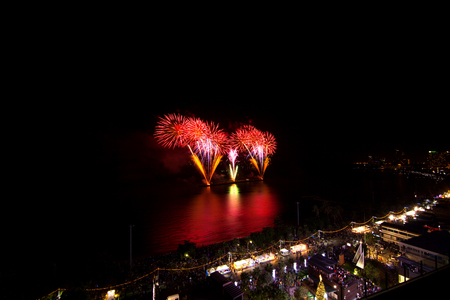 antecedents: Multicolor fireworks night scene, blurred photo pattaya cityscape sea beach view, thailand