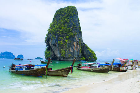 neighboring: Ao Nang  is a great spot to hitch a ride on a longtail boat to explore the magical neighboring beaches & islands, Railay, Koh Phi Phi, Poda Beach , Koh Chicken , Maya Beach.This picture have many ships. Editorial