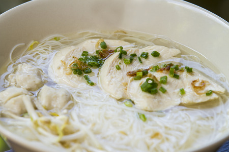 thai noodle soup: Thai noodle soup with fish ball in white ceramic bowl on brown wooden table - close up top view