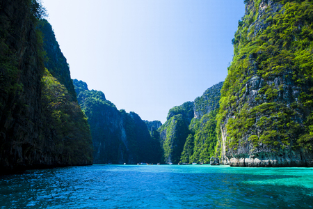 Thailand beach seascape with ring of steep limestone hills and traditional bright longtail boats parking, Maya Bay, Ko Phi Phi Lee island, Phi Phi archipelago, part of Krabi Province, Andaman Sea Stock Photo