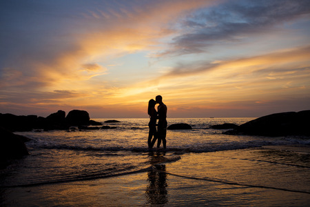 Couple kissing on the beach with a beautiful sunset in background Stock fotó