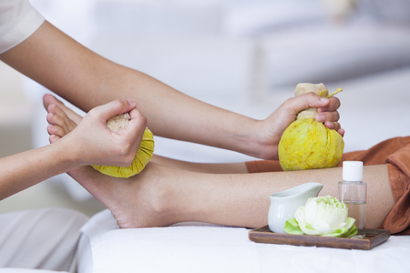 Beautiful young girl having massage with herbal balls in spa salon Stock fotó