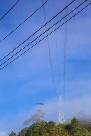 Power pole and power lines on blue sky background. Close up of power pole