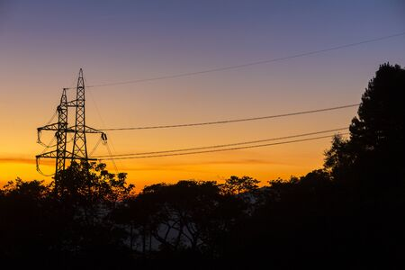 View of sunset in the evening against with the power poles and cables.