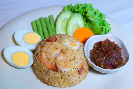 Sour Soup Fried Rice with Sea Bass,Dress the dish with fried fish, vegetables and boiled eggs.
