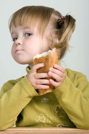 comiendo pan: muchacha bonita joven con el ponytail que come el pan Foto de archivo