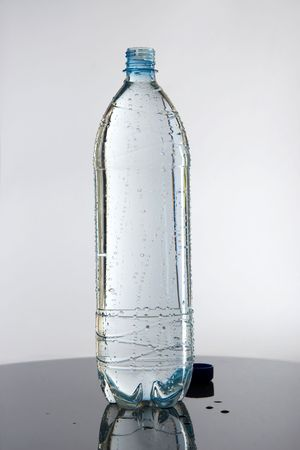 bottle with water: full bottle of water on glass Stock Photo