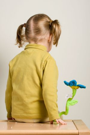 takings: child sitting on table with flower toy with it