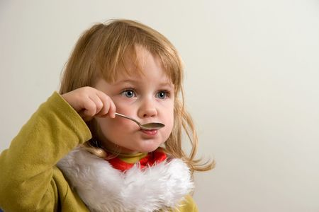 teaspoon: young cute girl eating with teaspoon