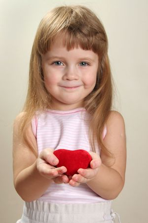 red heart in hands and slightly blurred child face ir background