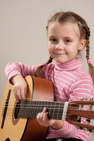 Young girl play classical guitar photo