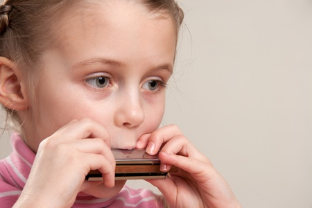 Young girl play blues harmonica Stock Photo