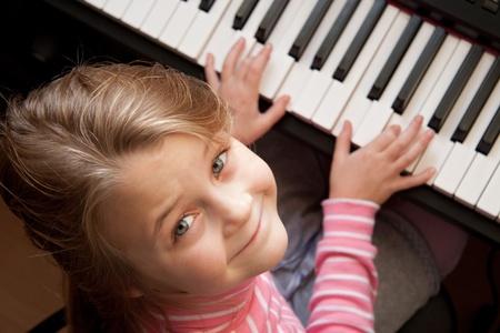 Young girl sitiing at digital  piano