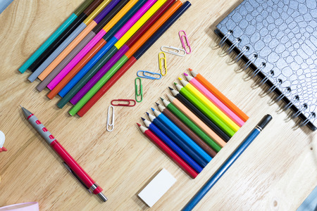 colorfully: Colorfully Office and art stationery objects on wood table with a notebook. Stock Photo