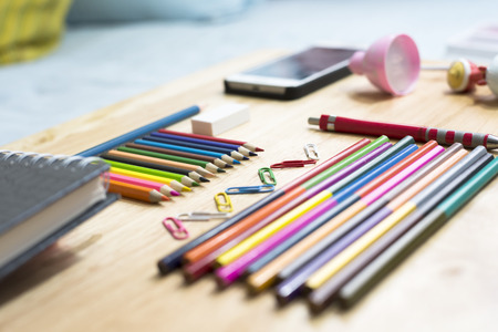 Colorfully Office and art stationery objects on wood table with a notebook. Stock Photo