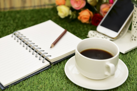 memo: Have a cup of black coffee.Writing on copy space note book . with Pencil on green grass Background.With selective focus. Stock Photo