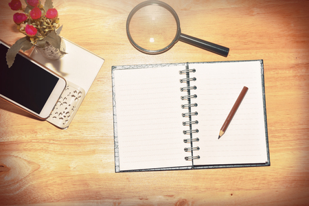 school notebook: Retro vintage  process.Business planning with copy space and office supplies.Have Blurry mobile and magnifying glasses ,mobile and glasses on wood background as props.