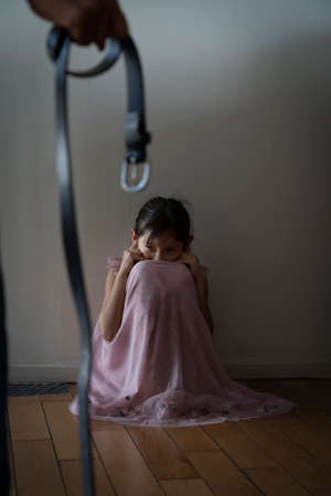 A belt in hand threatens a Sadness offended little girl scared. A Child sitting in a dark corridor in front of the door with light. Fear and indecisiveness. Domestic violence against a child concept.