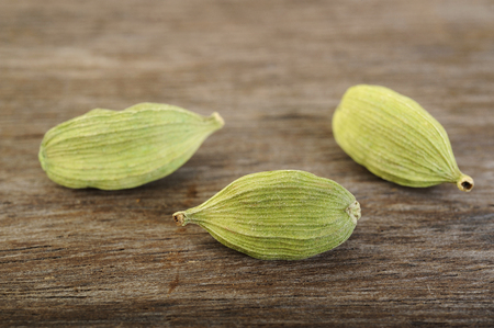 asian flavors: green cardamom pods on wooden background Stock Photo