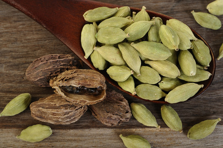 asian flavors: black and green cardamom in wooden spoon