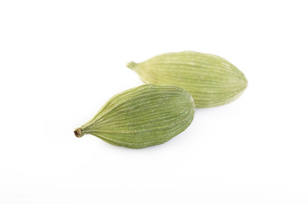 asian flavors: green cardamom pods isolated on white background