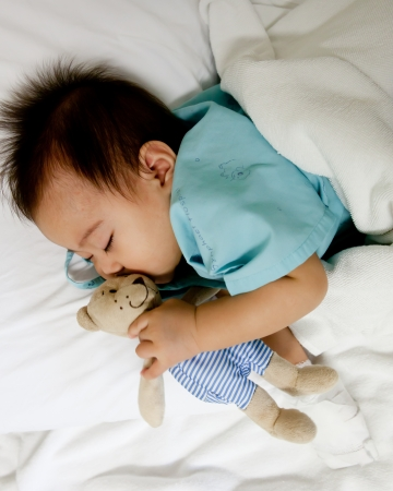 Sick little boy sleeping with his bear  doll Stock Photo