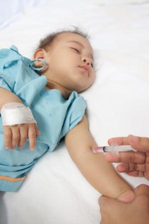 inyeccion intramuscular: Doctor que da a un ni�o una inyecci�n intramuscular en brazo, DOF Foto de archivo