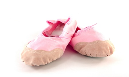 Small pink ballet slippers on a white background photo