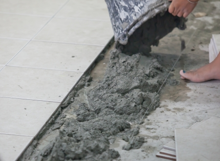 Spreading wet mortar before applying tiles on bathroom floor photo