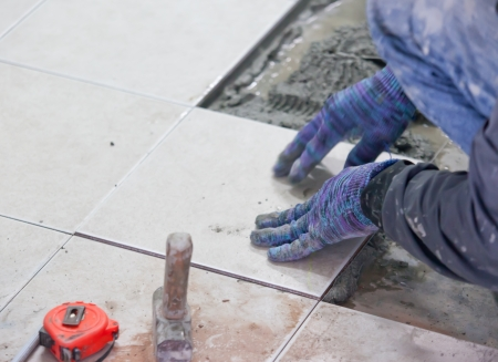 Man's hands placing a replacement ceramic tile photo