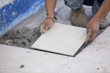 Mans hands placing a replacement ceramic tile photo