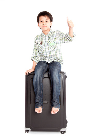 A little smiling boy with a suitcase is standing on the white background