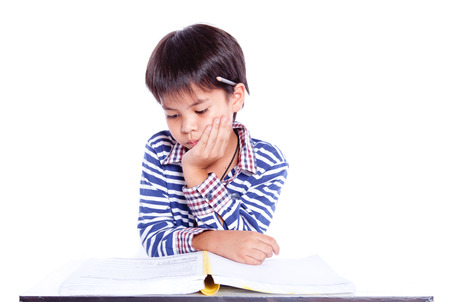 A young boy  in his homework or maybe writing a letter. Stock Photo - 27623709