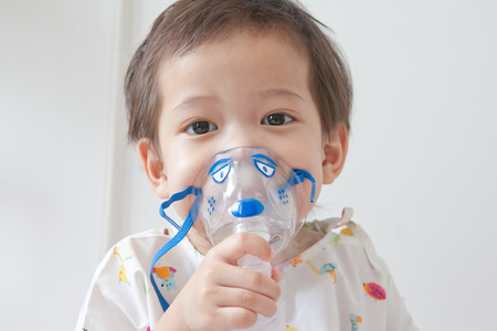 Little boy sick in hospital with a respiratory mask