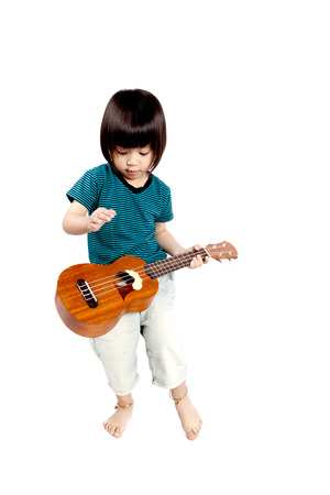 acoustic ukulele: boy is playing on acoustic ukulele on white background