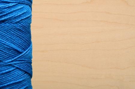 Blue yarn on wood background
