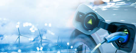 Double exposure of EV electric car charge battery uses nature electric energy from wind turbine to generate electricity. Bokeh light blue sky panoramic banner background copy space. Green eco concept.