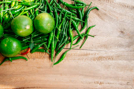 Green fresh chilli and lemons on wooden table with space for some text Stock Photo