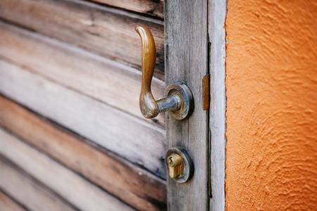 Close-up vintage style door handle of brass on old wooden door. Selective focus.
