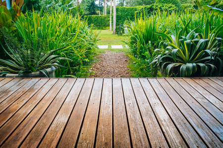 Wooden deck looks toward to tropical garden backyard.