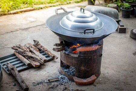 Aluminum steamer pot with big black pan on firewood burning stove for cooking thai dessert