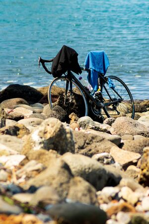 Manapany, France - September 27 2018 : Bicycle parked on stony beach while owner takes a swim