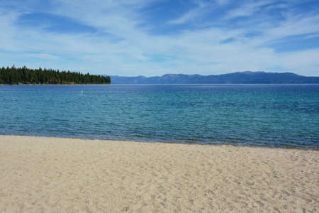 Seasonal perspective on Baldwin Beach along the shoreline of Lake Tahoe, California, with Sierra-Nevada mountain range shown on horizon.
