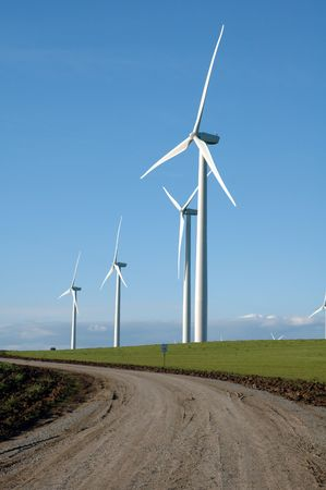 alternate: Dirt road leading up to a number of Alternate energy wind generators Stock Photo