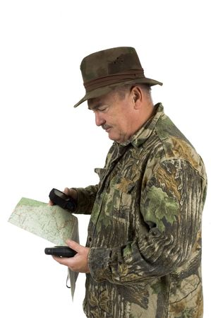 orienting: Man in Camouflage clothing using national forest maps and two gpss to check position on a white background