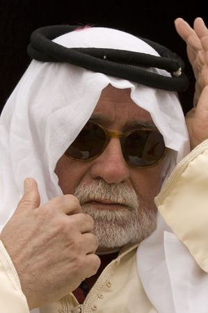 headress: Arabic looking gentleman in a dishdash, traditional headress and wearing sunglasses, making getures during conversation