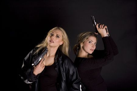 finger on trigger: two sexy woman with guns one down on black background Stock Photo